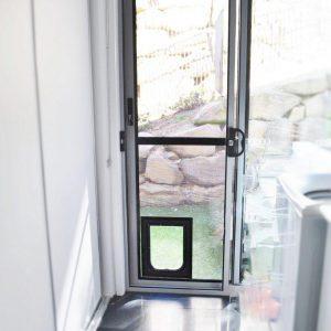 sliding crimsafe security door installed in laundry with pet door
